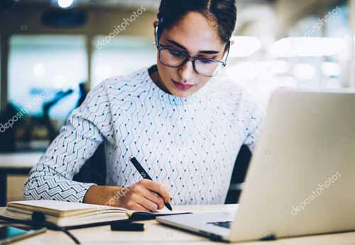 Pensive female administrative manager writing plan for project in notepad sitting at desktop with netbook, concentrated professional secretary assistant concentrated on accounting report in office